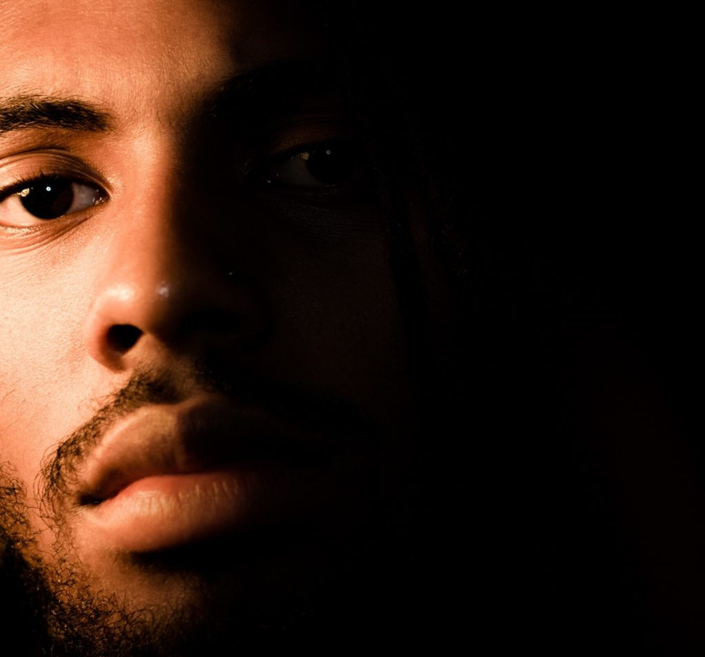 A close up of a black man's face with half covered in darkness.